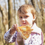 Schönes kleines Mädchen, das eine köstliche Pizza im Naturlebensmittel genießt stockbilder