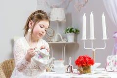 Schönes kleines Mädchen, das eine Teeparty hat Lizenzfreies Stockbild