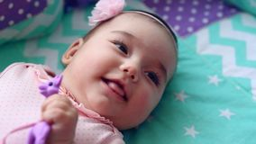 Schönes kleines Mädchen, das in einem Feldbett im Raum und im Lachen liegt stock video
