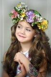 Schönes kleines Mädchen, das einen Kranz von Blumen trägt stockfotografie