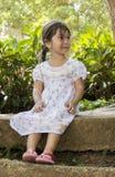 Schönes kleines Mädchen, das etwas beim Sitzen auf dem konkreten Rand eines allgemeinen Gartens betrachtet Lizenzfreie Stockfotos