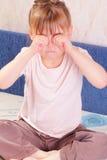 Schönes kleines Mädchen, das ihre Augen löscht Lizenzfreies Stockbild