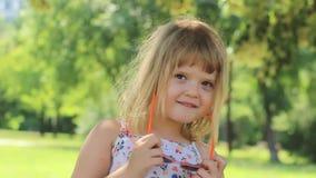 Schönes kleines Mädchen, das ihre Sonnenbrillen und das Lächeln beseitigt; positive Gefühle, Zeitlupe