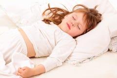 Schönes kleines Mädchen, das im Bett schläft stockfoto