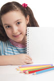 Schönes kleines Mädchen, das leeren Raum auf Notizbuch zeigt Lizenzfreie Stockfotografie