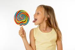 Schönes kleines Mädchen, das Lutscher auf weißem Hintergrund isst lizenzfreies stockbild