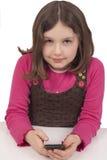 Schönes kleines Mädchen, das mit einem Handy spielt Lizenzfreie Stockfotos
