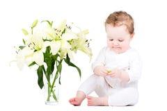 Schönes kleines Mädchen, das mit Lilienblumen spielt Lizenzfreie Stockbilder