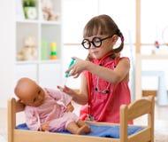 Schönes kleines Mädchen, das mit Spielzeugpuppe in der Kindertagesstätte spielt stockfotografie