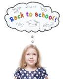 Schönes kleines Mädchen, das oben an zurück zu der Schule lokalisiert schaut Lizenzfreie Stockfotografie