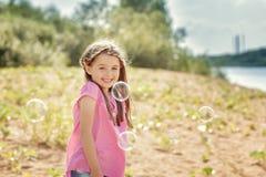 Schönes kleines Mädchen, das Spaß im Park hat Stockbild
