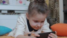 Schönes kleines Mädchen, das am Telefon, liegend auf einer gestrickten Wolldecke spielt und spielen mit einem Tablet-Computer stock video footage