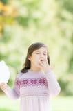Schönes kleines Mädchen, das Zuckerwatte im Park isst. Stockfoto