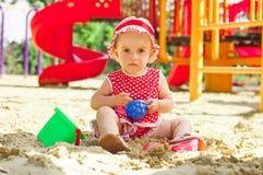 Schönes kleines Mädchen in der roten Kleidung, spielend Lizenzfreie Stockfotos