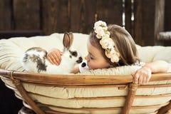 Schönes kleines Mädchen in einem Kranz von Blumen küsst einen netten flaumigen weißen Osterhasen lizenzfreies stockfoto