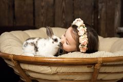 Schönes kleines Mädchen in einem Kranz von Blumen küsst einen netten flaumigen weißen Osterhasen stockbild