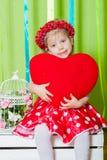 Schönes kleines Mädchen in einem roten Kleid mit einem roten Herzkissen Lizenzfreie Stockbilder