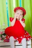 Schönes kleines Mädchen in einem roten Kleid mit einem roten Herzkissen Lizenzfreies Stockfoto