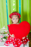Schönes kleines Mädchen in einem roten Kleid mit einem roten Herzkissen Stockfotos