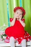 Schönes kleines Mädchen in einem roten Kleid mit einem roten Herzkissen Stockbild