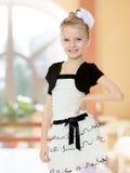 Schönes kleines Mädchen in einem weißen kurzen Kleid mit einem schwarzen Gürtel Lizenzfreie Stockfotografie