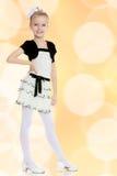 Schönes kleines Mädchen in einem weißen kurzen Kleid mit einem schwarzen Gürtel Lizenzfreies Stockfoto
