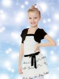 Schönes kleines Mädchen in einem weißen kurzen Kleid mit einem schwarzen Gürtel Stockbilder