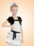 Schönes kleines Mädchen in einem weißen kurzen Kleid mit einem schwarzen Gürtel Stockfotos
