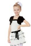 Schönes kleines Mädchen in einem weißen kurzen Kleid mit einem schwarzen Gürtel Lizenzfreies Stockbild