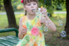 Schönes kleines Mädchen im Farbkleid brennt Blasen durch lizenzfreies stockbild