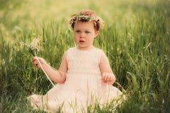 Schönes kleines Mädchen im Kranz von Blumen Stockbilder