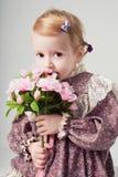 Schönes kleines Mädchen im Retro Kleid mit Blumenstrauß der Blumen Stockfotos