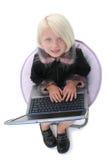 Schönes kleines Mädchen im Stuhl mit Laptop-Computer stockfoto