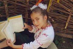 Schönes kleines Mädchen 7 Jahre in der Stickerei bucht lizenzfreie stockfotos