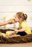 Schönes kleines Mädchen küsst ein nettes flaumiges Ostern-Entlein stockbild