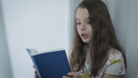 Schönes kleines Mädchen lernt ein Gedicht durch Fenster stock footage