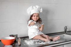 Schönes kleines Mädchen lernt, eine Mahlzeit in der Küche zu kochen stockfotografie
