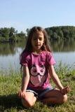 Schönes kleines Mädchen meditiert in der Natur Lizenzfreie Stockbilder