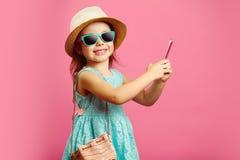Schönes kleines Mädchen mit bezauberndem Lächeln betrachtet Sie, angekleidet im modernen blauen Kleid und trägt einen Strandhut u lizenzfreies stockfoto