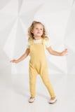 Schönes kleines Mädchen mit dem blonden Haar, im gelben Overall auf weißem Hintergrund Stockfotografie