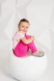 Schönes kleines Mädchen mit dem blonden Haar, im rosa Overall auf weißem Hintergrund Lizenzfreies Stockbild