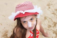 Schönes kleines Mädchen mit dem Hut, der auf dem Strand aufwirft Stockfotografie