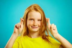 Schönes kleines Mädchen mit dem roten Haar und den Sommersprossen macht einen Wunsch, die gekreuzten Finger, glaubt an Erfüllung  Lizenzfreie Stockfotografie