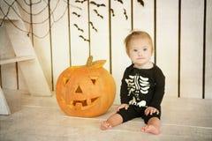 Schönes kleines Mädchen mit Down-Syndrom, das nahe einem Kürbis auf Halloween sitzt, kleidete als Skelett an stockfotografie