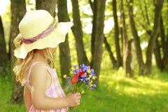 Schönes kleines Mädchen mit einem Blumenstrauß von Blumen in der Natur Stockfotografie