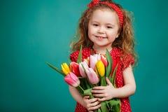 Schönes kleines Mädchen mit einem großen Blumenstrauß von Tulpen Lizenzfreie Stockbilder