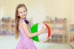 Schönes kleines Mädchen mit einem großen mehrfarbigen aufblasbaren Ball Lizenzfreie Stockbilder