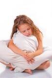 Schönes kleines Mädchen mit einem Kissen stockfoto