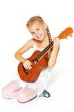 Schönes kleines Mädchen mit einer Gitarre lizenzfreie stockbilder