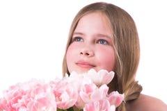 Schönes kleines Mädchen mit rosafarbenen Tulpen Stockfotografie